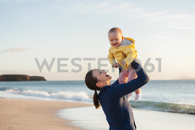 Mother lifting up little daughter on the beach - DIGF03241