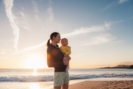 Mother holding little daughter on the beach at sunset - DIGF03244
