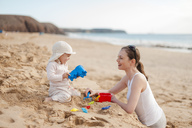 Mother playing with little daughter on the beach - DIGF03253