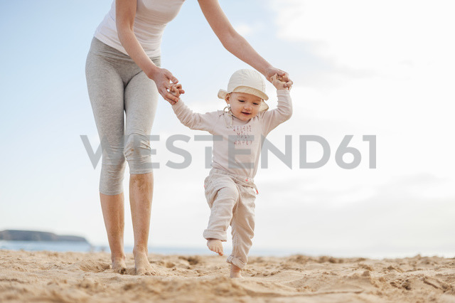 Mother helping little daughter walking on the beach - DIGF03256