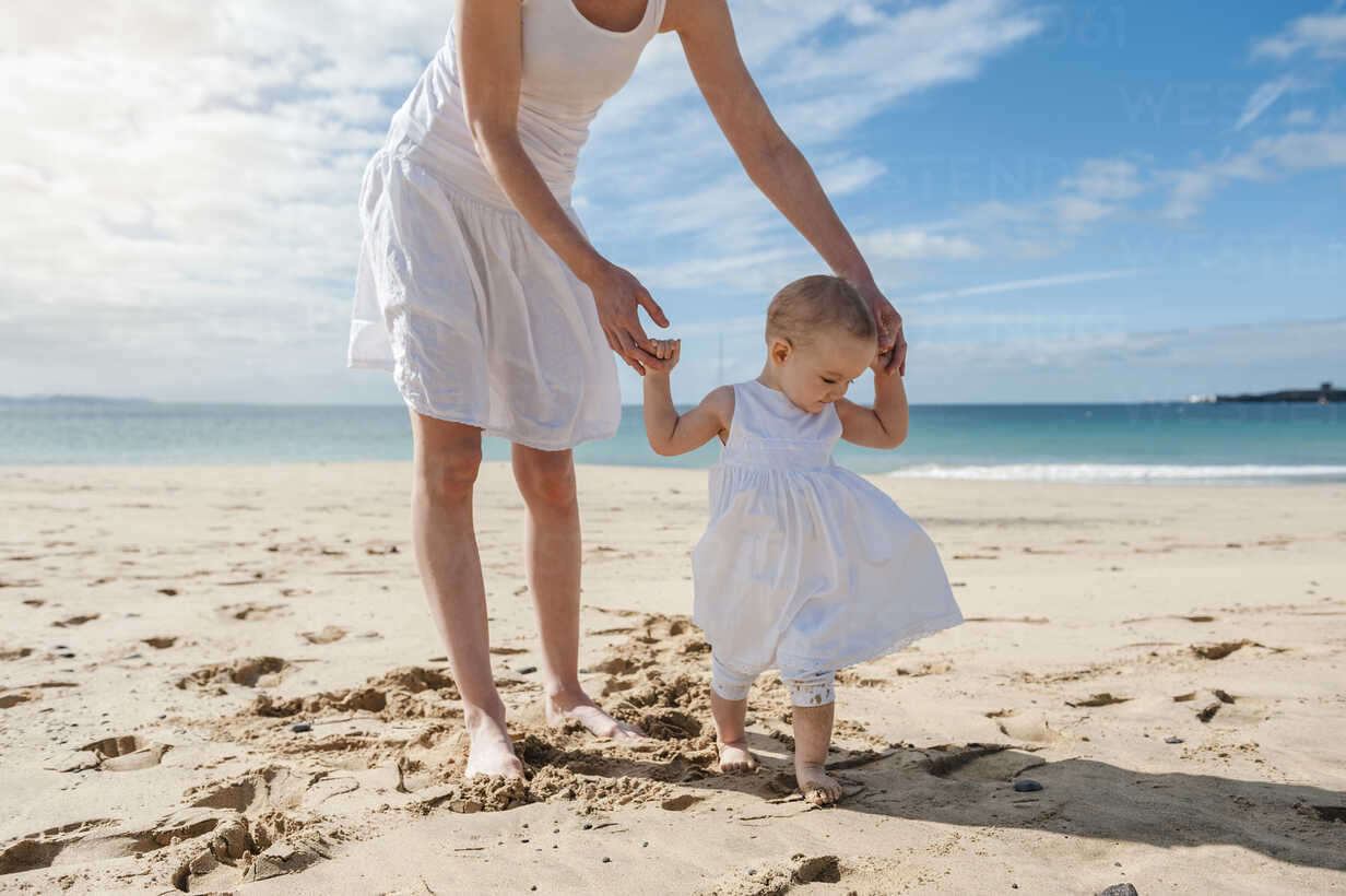Mother helping little daughter walking on the beach - DIGF03259 - Daniel Ingold/Westend61