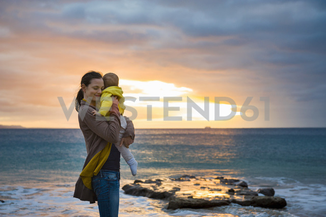 Mother holding little daughter on the beach at sunset - DIGF03268