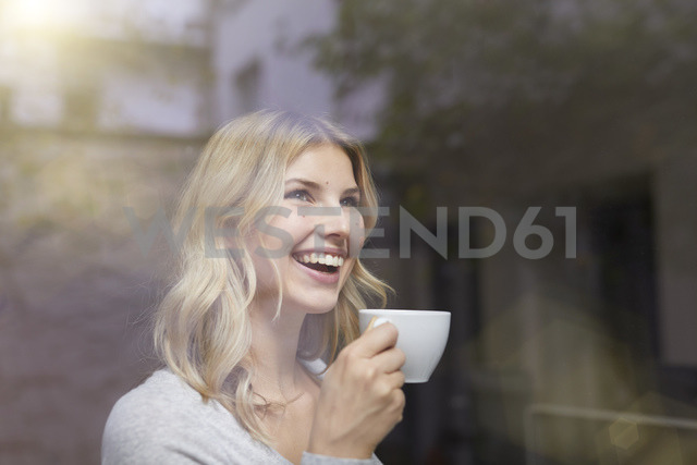 Portrait of laughing woman with cup of coffee behind windowpane - PNEF00519