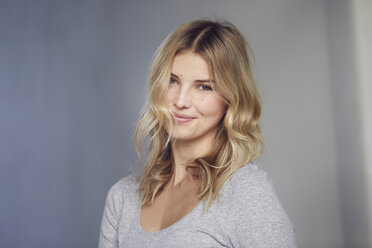 Portrait of smiling blond woman in front of grey background - PNEF00522