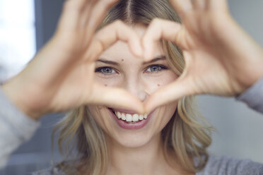 Portrait of laughing woman building heart with her fingers - PNEF00525