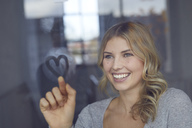 Portrait of happy blond woman drawing heart on windowpane - PNEF00528