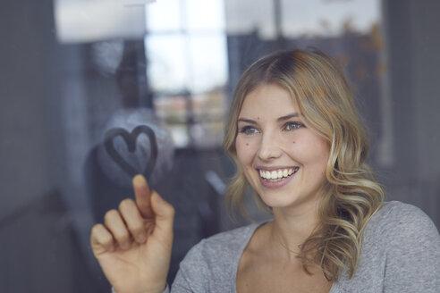 Portrait of happy blond woman drawing heart on windowpane - PNEF00528
