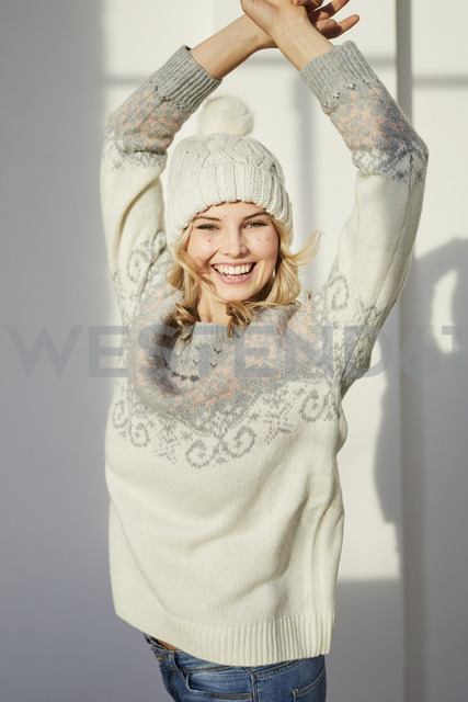 Portrait of laughing woman wearing knit pullover and bobble hat - PNEF00531