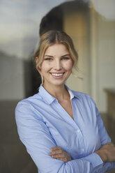 Portrait of content businesswoman behind windowpane - PNEF00534