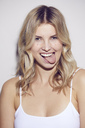 Portrait of blond woman sticking out tongue - PNEF00537