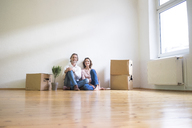 Smiling mature couple sitting on floor in empty room next to cardboard boxes - MOEF00741