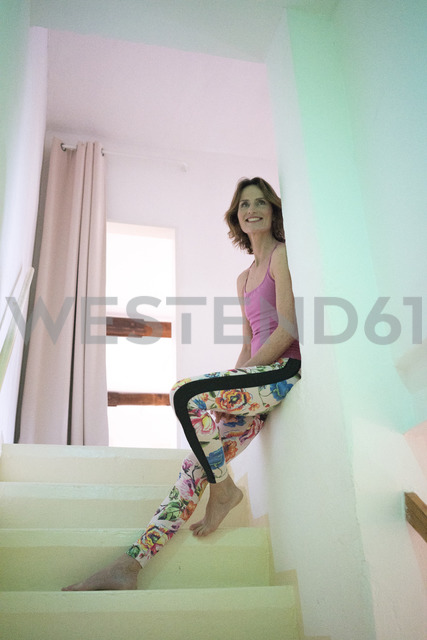 Smiling mature woman leaning against a wall in staircase - MOEF00750