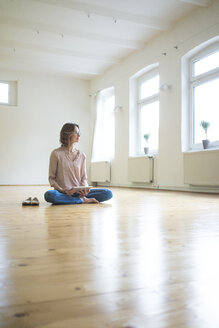 Mature woman sitting on floor in empty room with tablet - MOEF00753