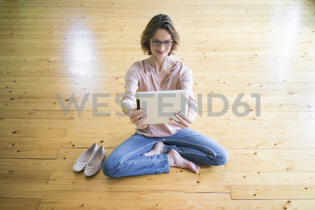 Smiling mature woman sitting on wooden floor taking selfie with tablet - MOEF00756