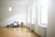 Mature couple sitting on floor in empty room next to cardboard boxes using tablet - MOEF00762