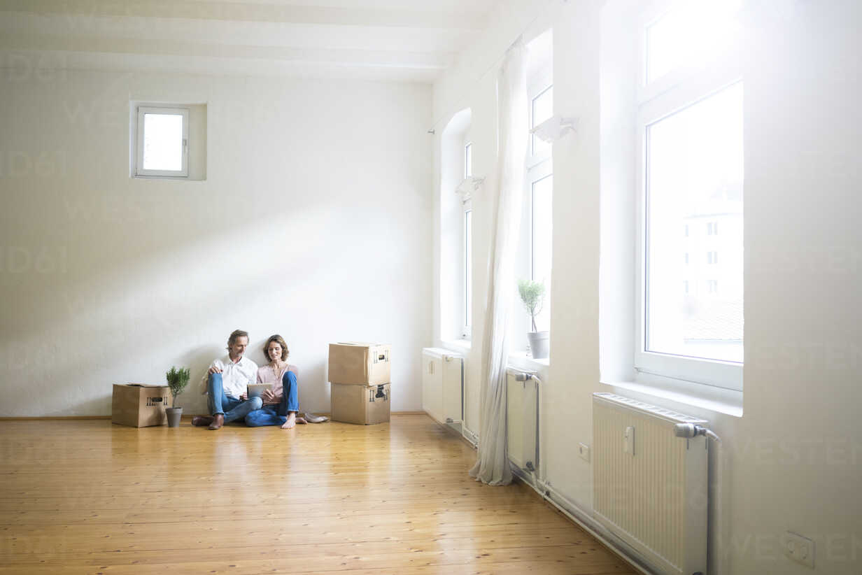 Mature couple sitting on floor in empty room next to cardboard boxes using tablet - MOEF00762 - Robijn Page/Westend61