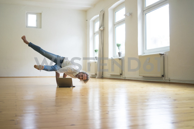 Mature man doing a handstand on floor in empty room looking at tablet - MOEF00765