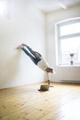 Mature man doing a handstand on floor in empty room looking at tablet - MOEF00768
