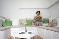 Relaxed mature woman on bench reading a book - MOEF00771