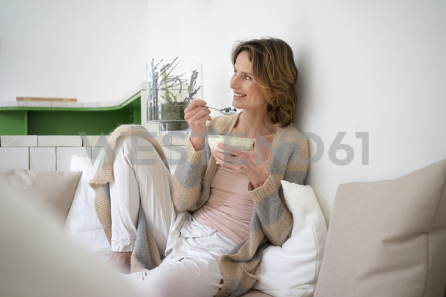 Relaxed smiling mature woman sitting on bench eating healthy food - MOEF00774