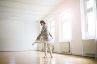 Happy mature woman standing in empty room in sunlight - MOEF00777