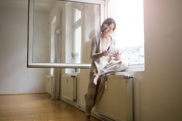 Mature woman in empty room using tablet at the window - MOEF00780