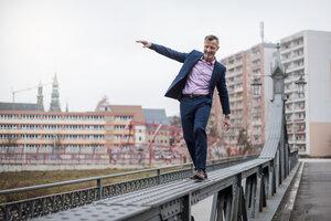 Stylish mature businessman wearing blue suit balancing on railing of bridge - DIGF03279
