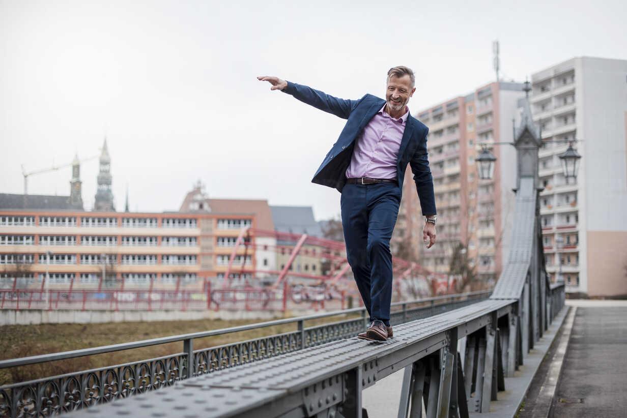 Stylish mature businessman wearing blue suit balancing on railing of bridge - DIGF03279 - Daniel Ingold/Westend61