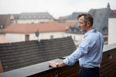 Mature businessman standing on roof terrace looking at view - DIGF03282