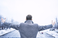 Back view of man with arms outstretched standing on bridge above motorway - BSZF00231