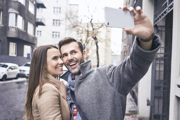 Happy couple taking selfie in the city - BSZF00234