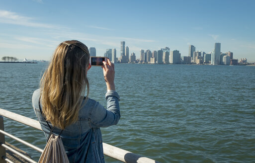 USA, New York, woman taking cell phone picture of New Jersey skyline - SEEF00003