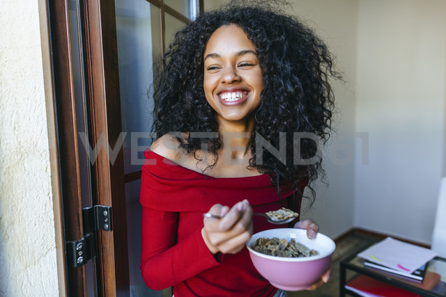 Portrait of laughing young woman eating cereals - KIJF01894