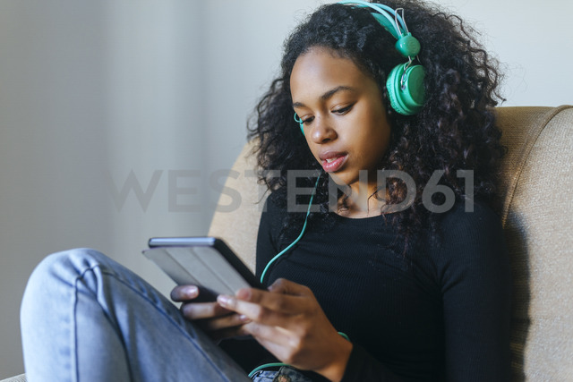 Portrait of young woman sitting in armchair listening music with headphones and tablet - KIJF01906