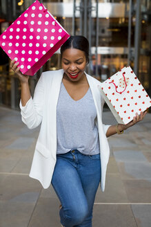 Happy woman holding shopping bags - MAUF01339