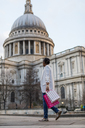 UK, London, woman walking with shopping bags at  St Paul's Cathedral - MAUF01342