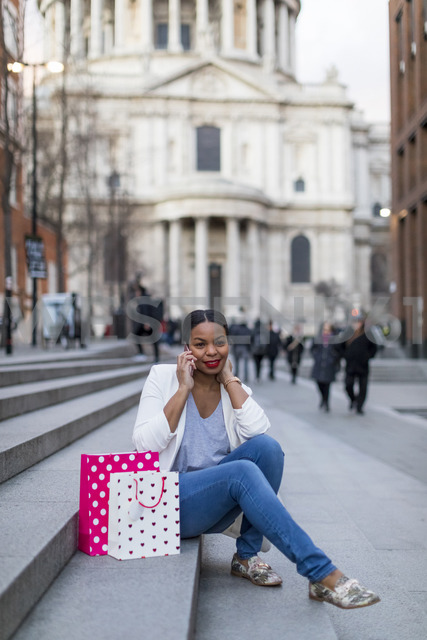 UK, London, woman with shopping bags on cell phone sitting on stairs in the city - MAUF01345