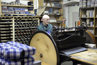 Senior shoemaker working with old-fashioned punching machine in workshop - BFRF01811