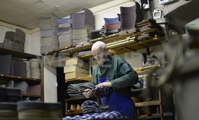 Senior shoemaker working on slippers in workshop - BFRF01820