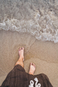 Thailand, feet of man standing on the beach at seaside - KKAF00863