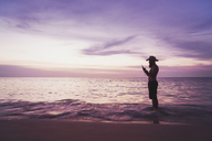 Thailand, Phuket, silhouette of bearded man standing at seaside by sunset using cell phone - KKAF00866
