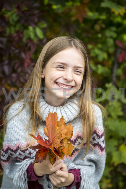 Portrait of laughing girl holding bunch of autumnal leaves - SARF03552