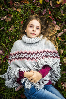 Portrait of girl wearing poncho lying on autumnal meadow - SARF03555