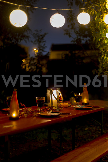 Laid table in garden at night - SARF03558