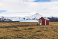 Iceland, Vik, Barn in the countryside with glacier in background - WPEF00103