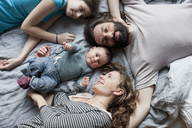 High angle view of family relaxing on bed - FSIF00029