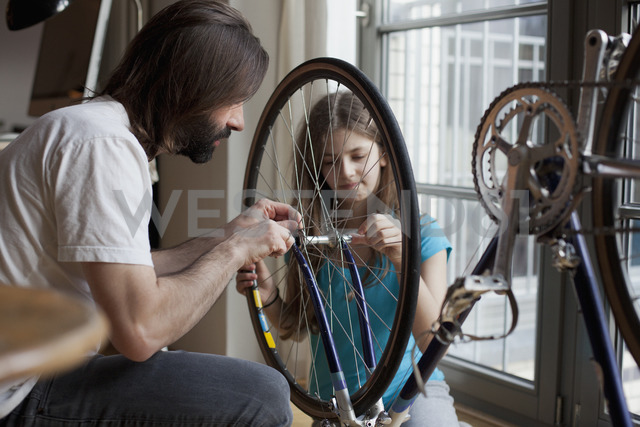 Father and daughter repairing bicycle together at home - FSIF00035 - fStop/Westend61