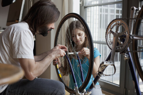 Father and daughter repairing bicycle together at home - FSIF00035