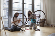 Father and daughter fixing bicycle together at home - FSIF00038