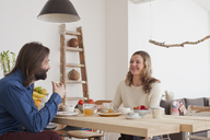 Smiling couple having breakfast at home - FSIF00056
